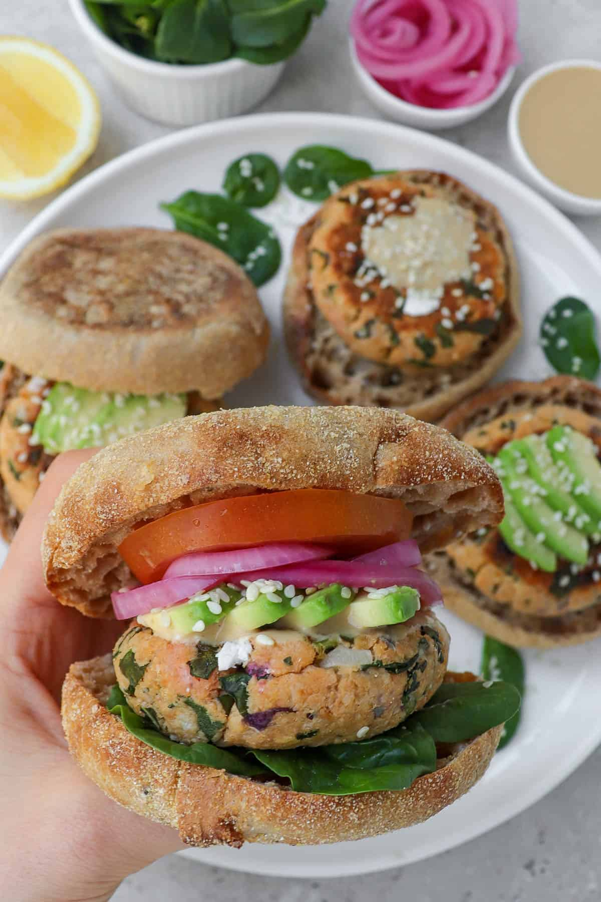 Holding salmon patty English muffin burger in hand. Topped with avocado, red pickled onions and tomato.