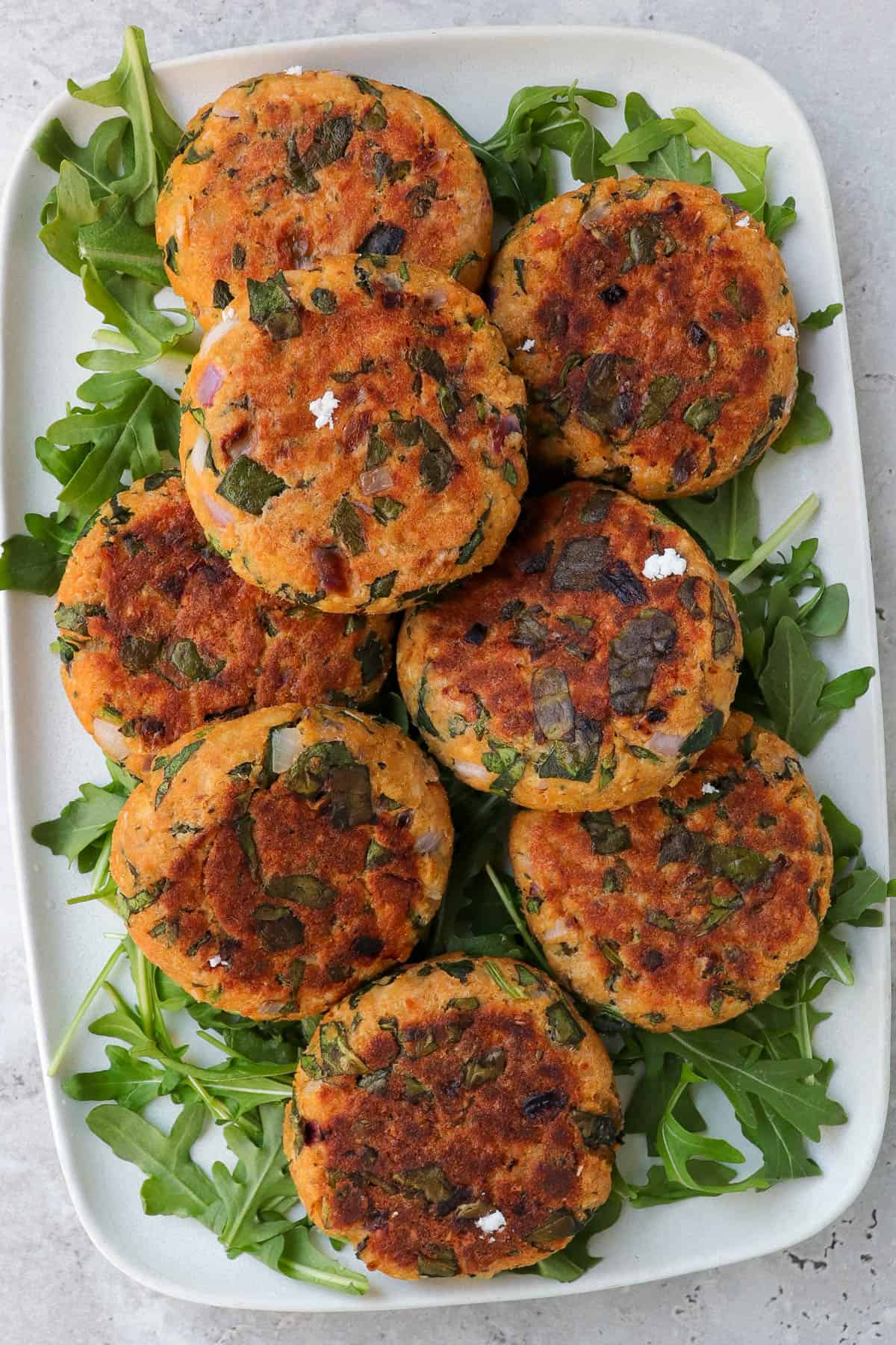 cooked salmon patties on platter with rocket leaves.