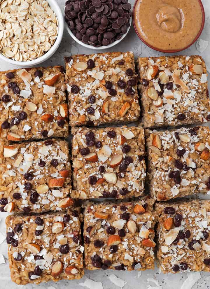 Almond joy baked oatmeal cut into squares with oats, chocolate chips, almond butter and coconut chips around for decoration.