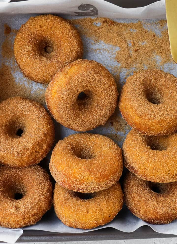 Donuts in the tray with a knife.